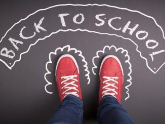 Sidewalk chalk written back to school with student's shoes shown