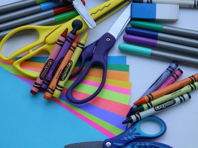 Scattered crayons, scissors, and paper